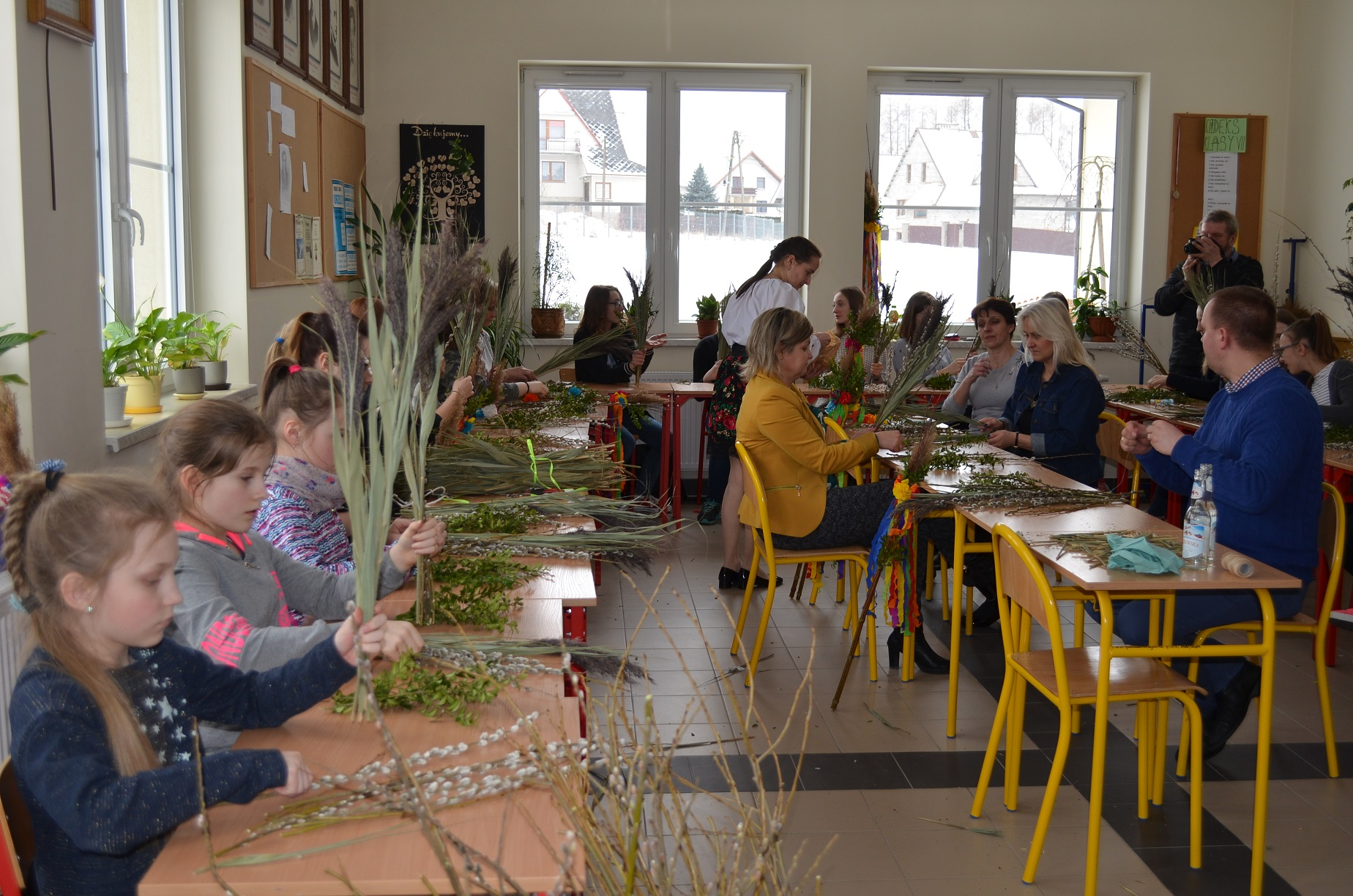 Sala szkolna. Przy stolikach siedzą dzieci i dorośli. Trzymają w dłoniach wiązki trawy stawowej. Przed nimi leżą gałązki bukszpanu i wierzby z baziami