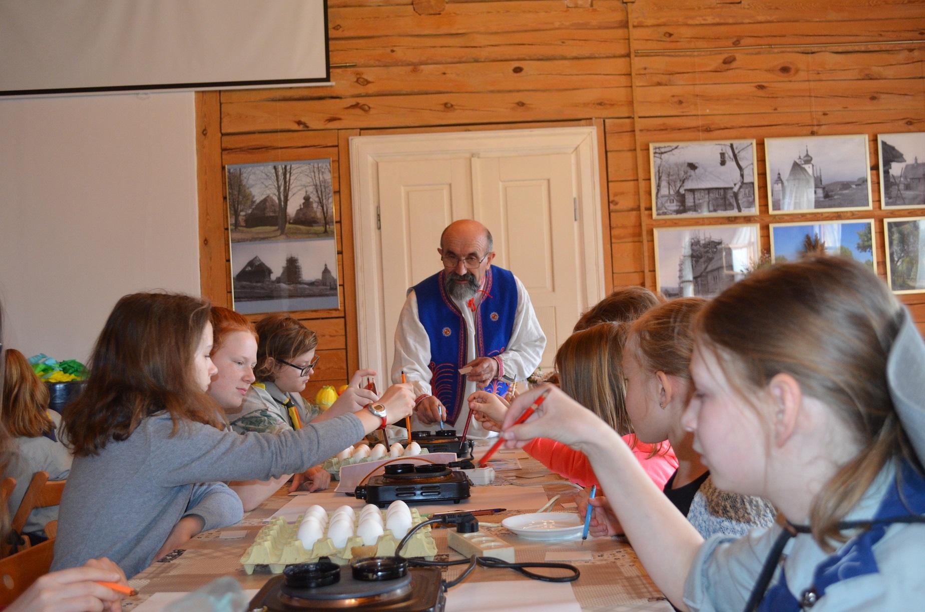 Dziewczynki siedzące przy długim stole w dłoniach trzymają ołówki zakończone szpilkami. Zanurzają je w roztopionym wosku