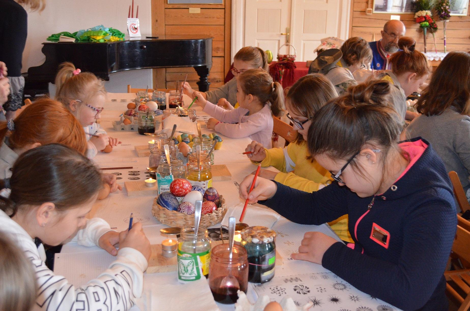 Dziewczynki siedzące przy długim stole rysują roztopionym woskiem na kartkach papieru za pomocą ołówków zakończonych szpilkami