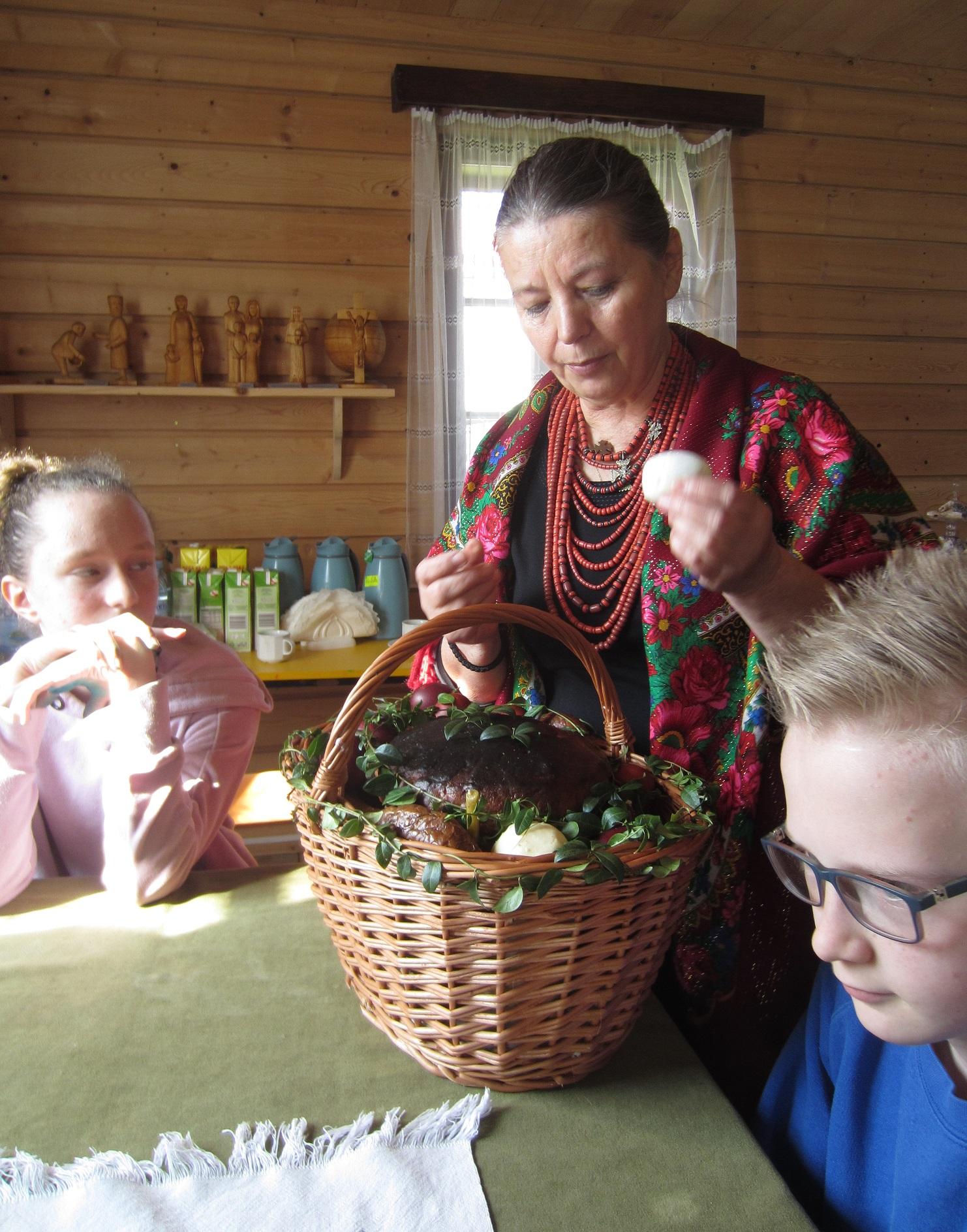 Kobieta w długich czerwonych koralach i czerwonej wzorzystej chuście na ramionach. Przed nią na stole leży koszyk ozdobiony bukszpanem, a w nim znajduje się duża bułka, kiełbasa i jajka.