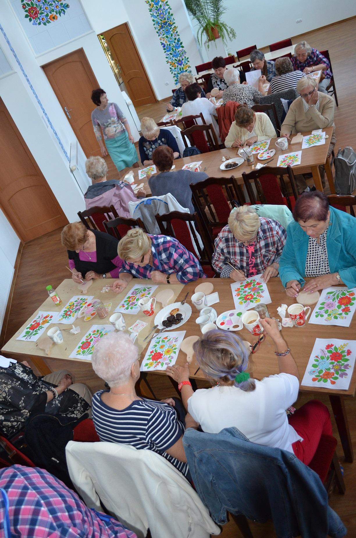 Duża sala. W niej kilka stołów, przy których siedzą kobiety w wieku około 60 lat. Na kartkach papieru lub drewnianych deseczkach malują kolorowe kwiatowe wzor
