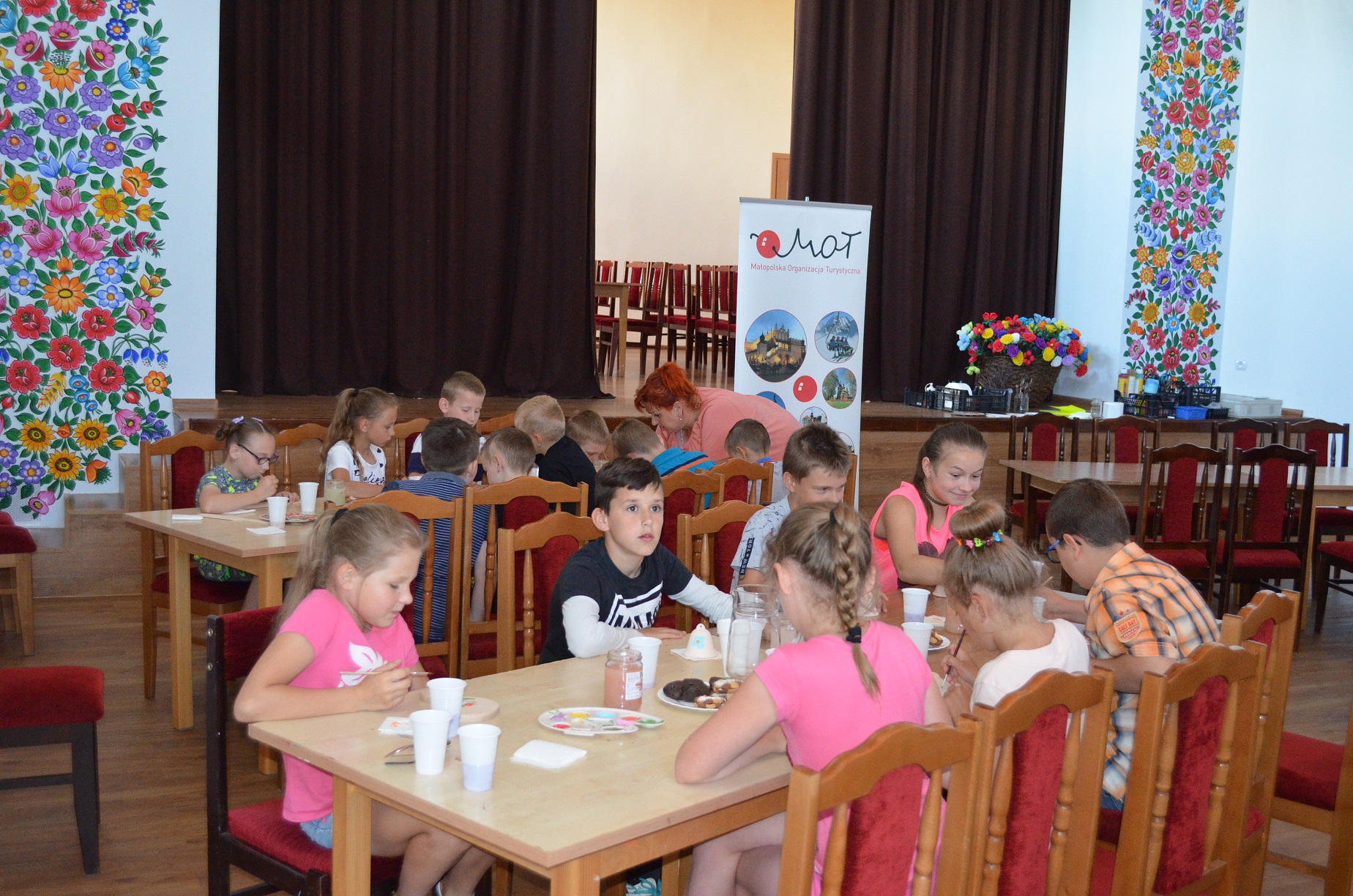 Duża sala. W niej kilka stołów, przy których siedzą dzieci. W dłoniach trzymają pędzle