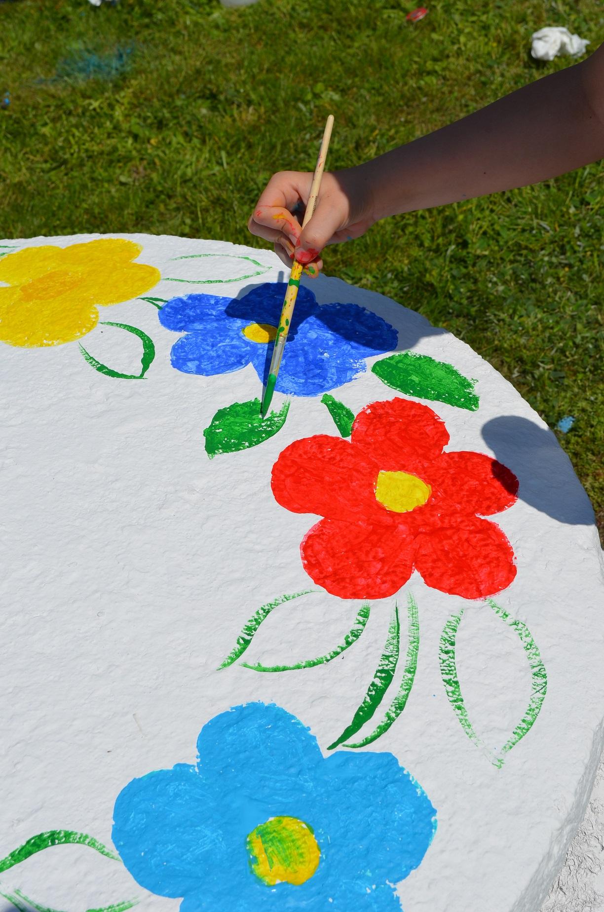 Wielko studni pomalowane na biało z kilkoma wymalowanymi kwiatami i konturami liści. Dłoń pędzlem wypełnia farbą wzór liścia
