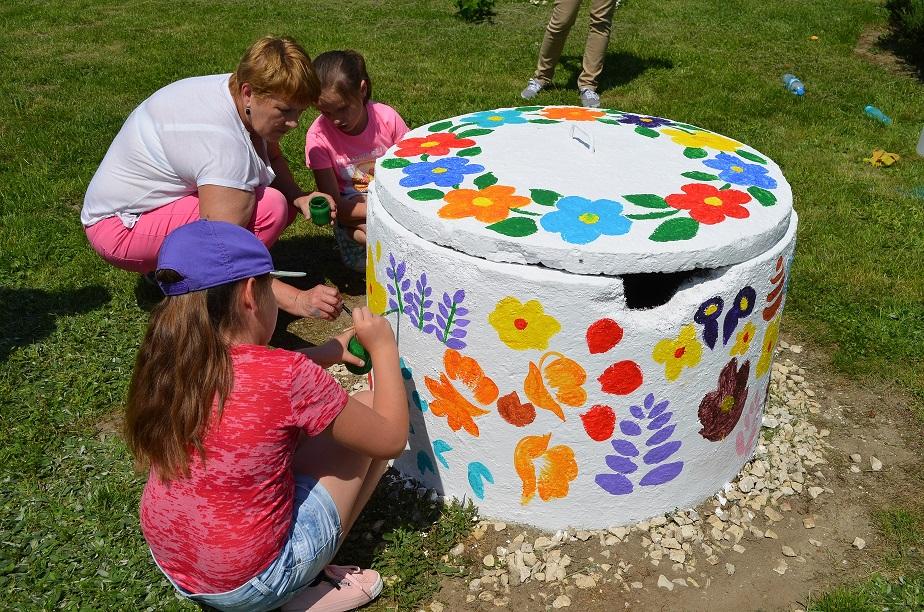 Studnia pomalowana na biało, z kolorowymi wzorami kwiatowymi. Kucają przy niej dwie dziewczynki i kobieta. Na studnię za pomocą pędzli nanoszą wzory