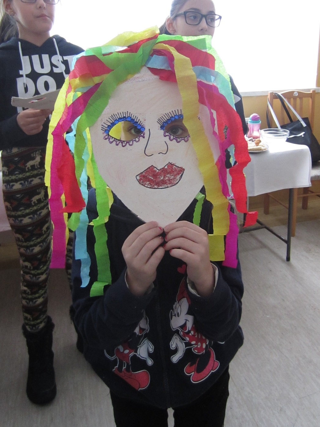 dziewczynka przykłada do twarzy maskę z kartonu z wyciętymi otworami na oczy i różnokolorowymi pasami bibuły przyklejonymi do górnej części maski i zwisającymi po obu jej stronach