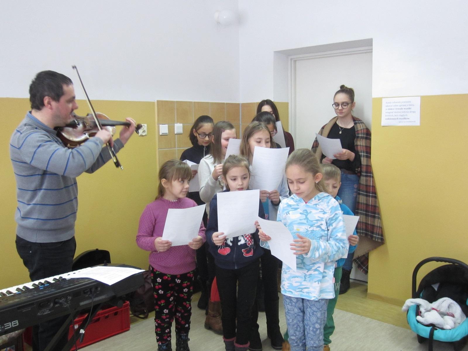 grupa dziesięciu dzieci. Każde z nich spogląda na trzymaną przed sobą kartkę papieru. Obok mężczyzna grający na skrzypcach.