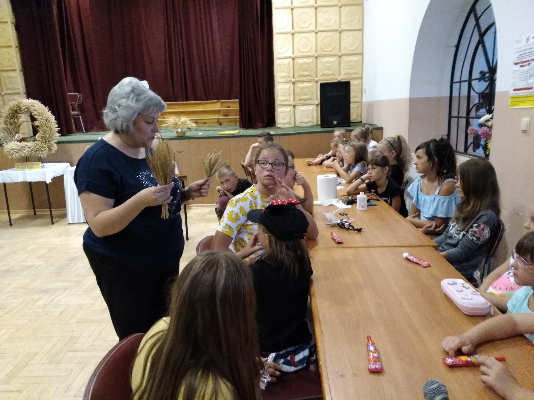 duża sala. Pod ścianą równolegle do niej ustawiono kilka stołów, przy których siedzą dzieci. Obok nich stoi kobieta. Trzyma w dłoniach dwie wiązki zboża