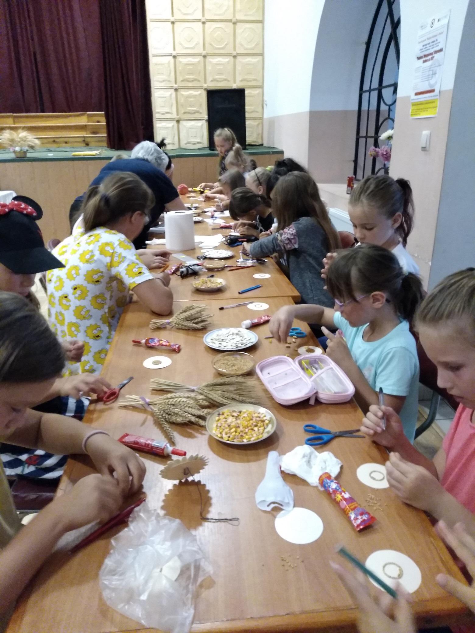 przy długim stole siedzi około dwudziestki dzieci. Na małych okrągłych karteczkach za pomocą różnego rodzaju ziaren tworzą wzory kwiatów