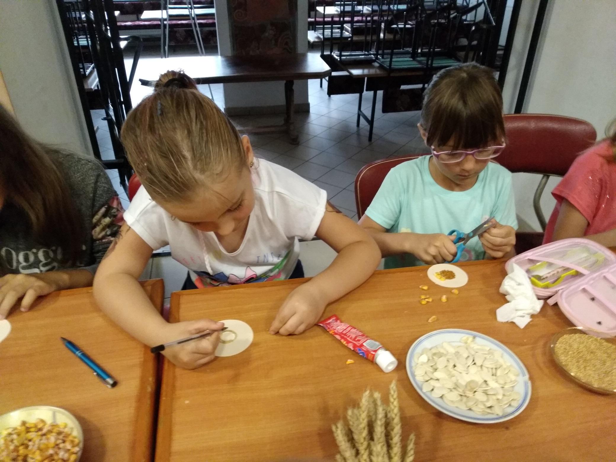 przy stole siedzą dwie dziewczynki. Na małych okrągłych karteczkach za pomocą różnego rodzaju ziaren tworzą wzory kwiatów