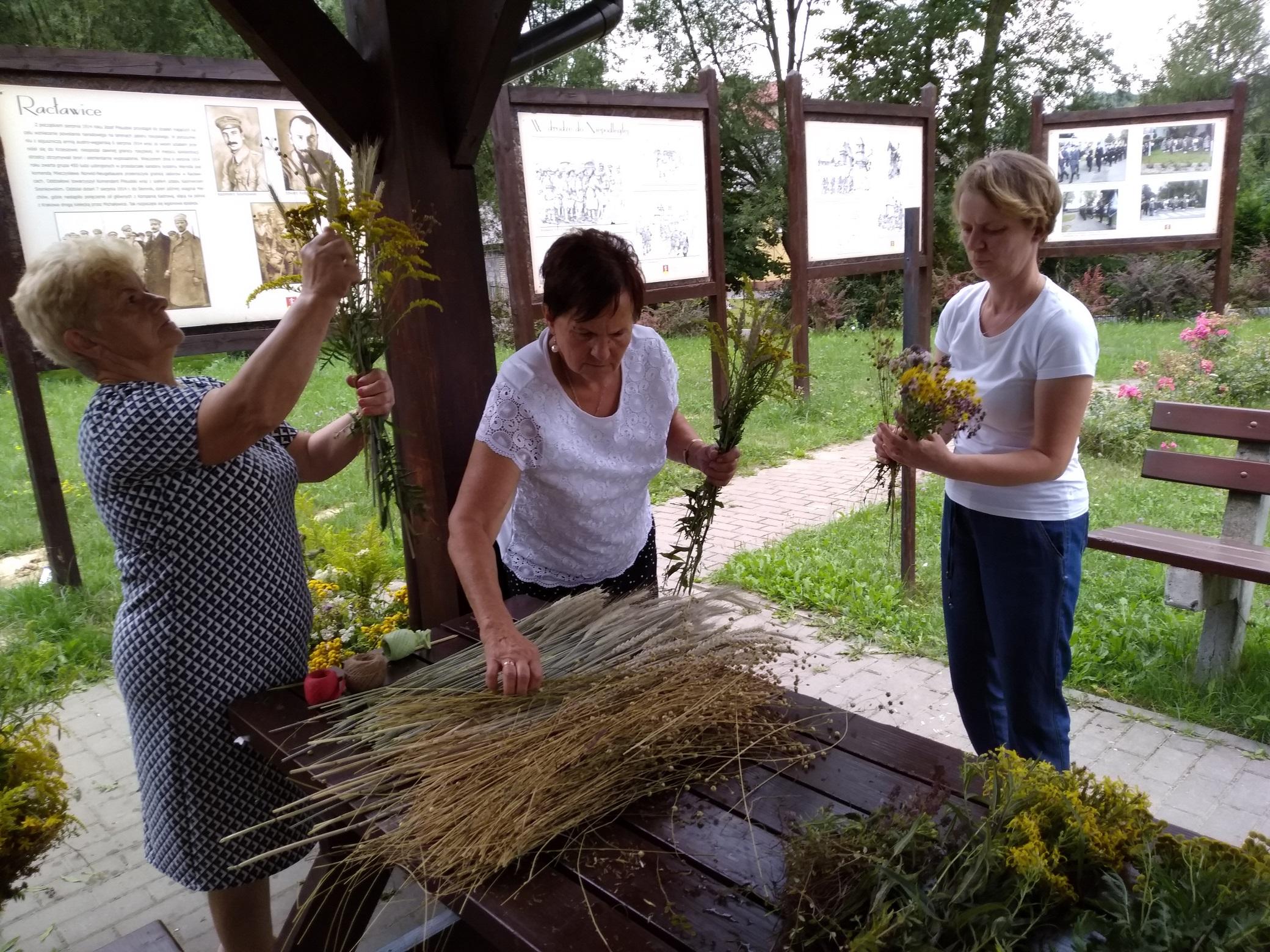 na drewnianym stole leżą wiązki różnych zbóż. Trzy kobiety wybierają poszczególne kłosy i dokładają je do bukietów trzymanych w dłoniach