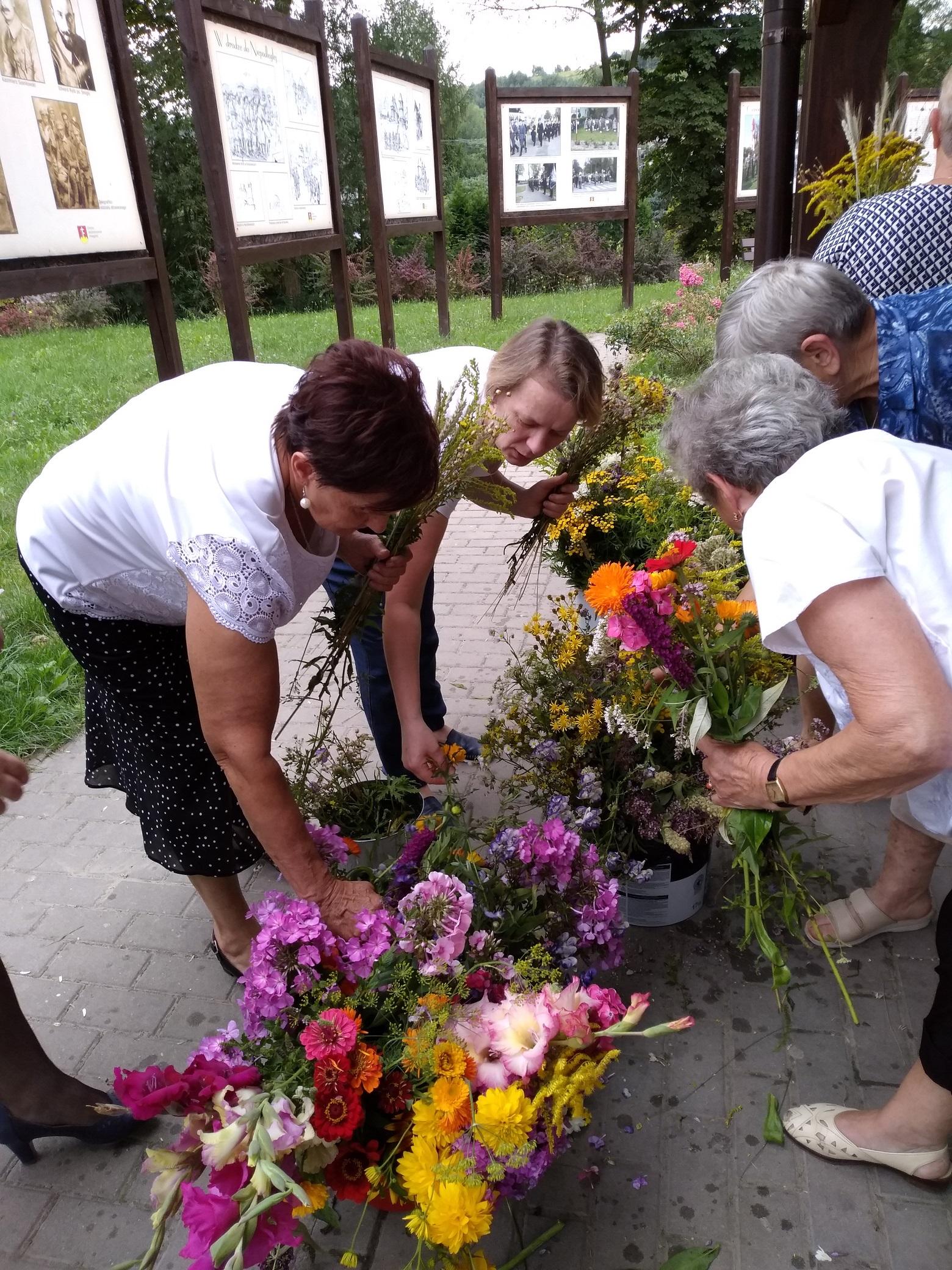w kilku pojemnikach znajduje się wiele różnych kwiatów i ziół. Kilka kobiet wybiera poszczególne rośliny i dokłada je do bukietów trzymanych w dłoniach