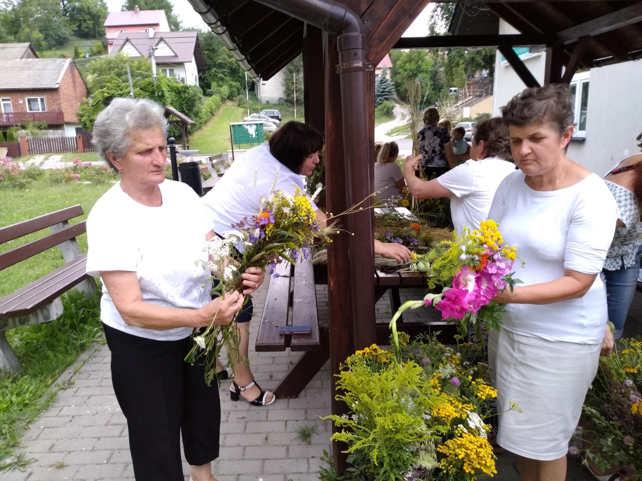 dwie kobiety układają trzymane w dłoniach bukiety