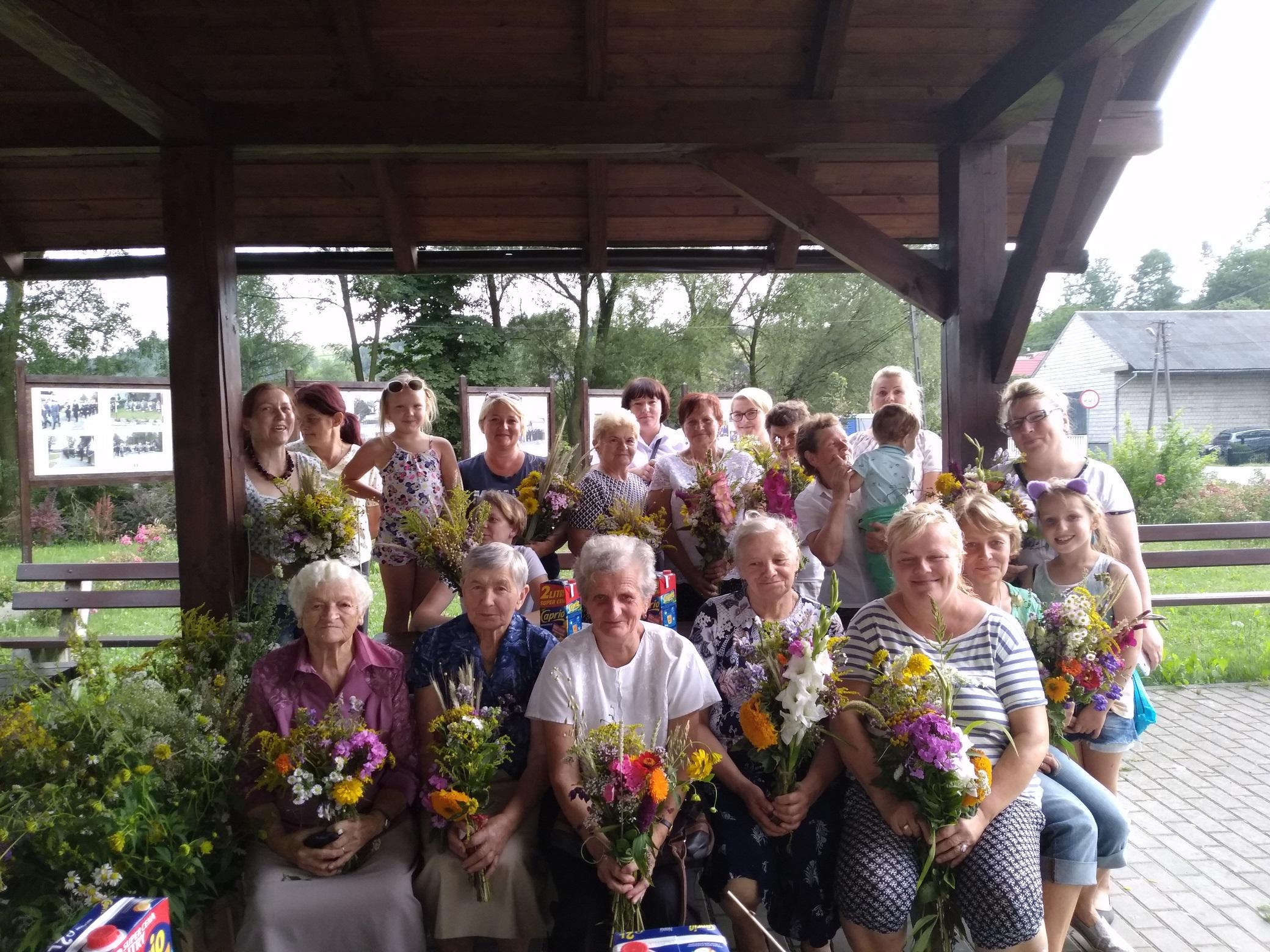 grupa około dwudziestu kobiet. Każda z nich trzyma w dłoniach bukiet z kwiatów i ziół.